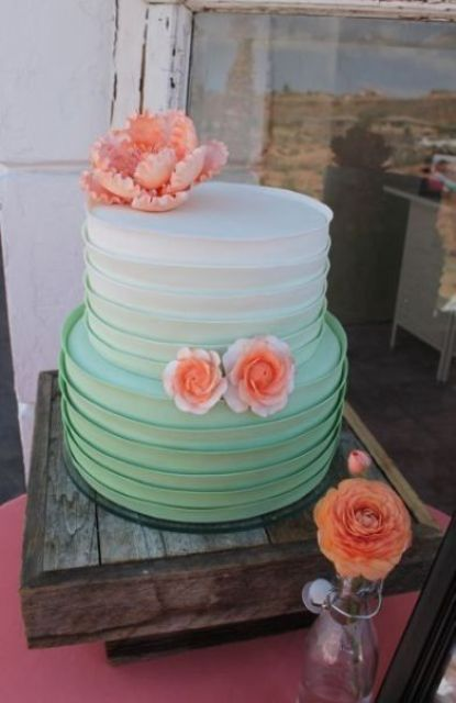 a ruffled ombre wedding cake from white to mint green topped with sugar coral blooms