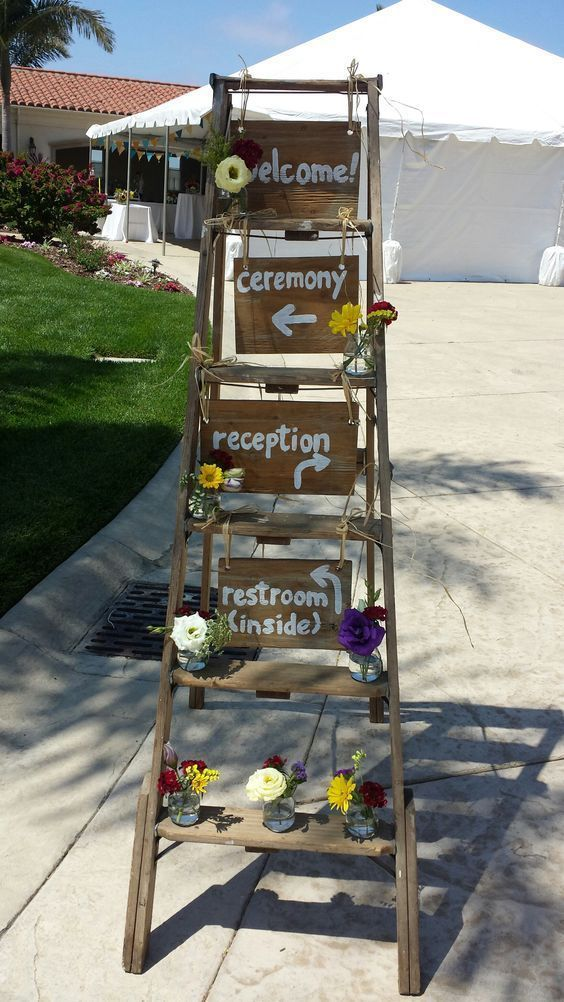 a rustic wedding decoration of a ladder, bright blooms and greenery and plywood signs is easy to DIY