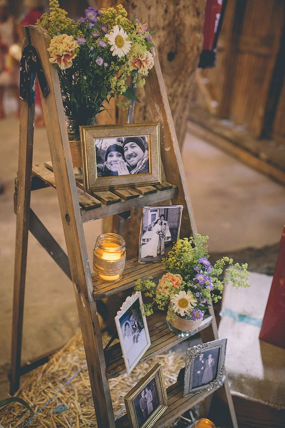 a rustic wedding decoration of a ladder, bright blooms and greenery, candles and family photos in frames