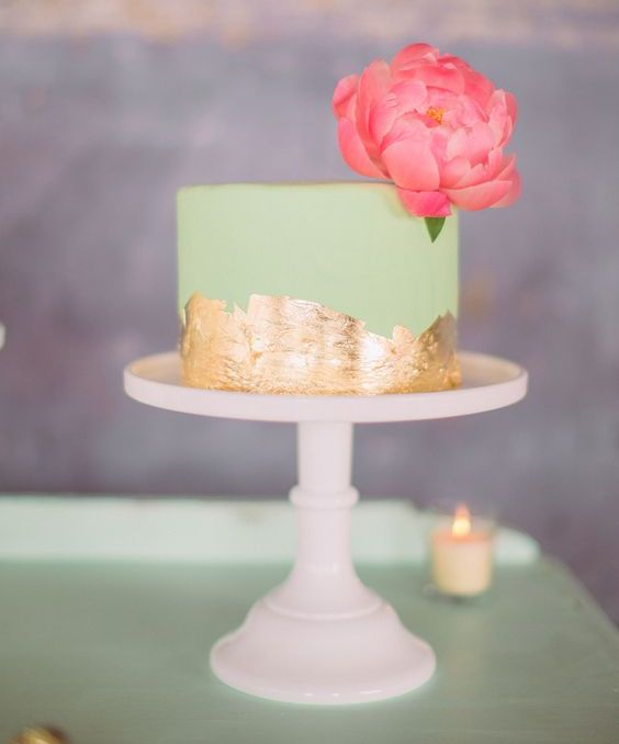 a small mint green wedding cake with gold leaf and a large pink bloom on top