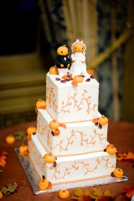a square white buttercream wedding cake with patterns, sugar pumpkins and leaves plus pumpkin cake toppers