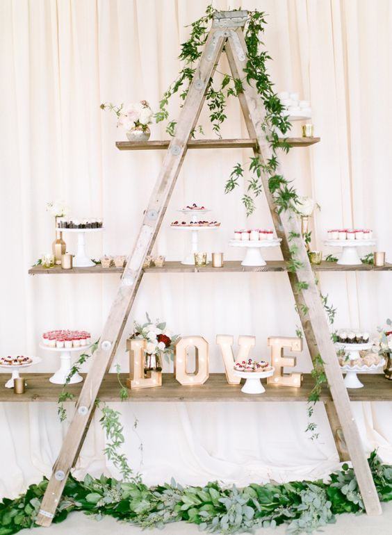a stylish rustic wedding dessert bar of a ladder interwoven with greenery, with marquee lights and lots of delicious desserts