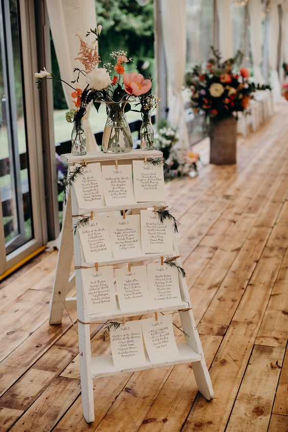 a stylish seating chart with paper, greenery and some white and pink blooms in vases on top