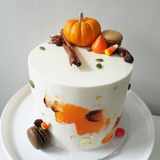 a stylish white buttercream wedding cake topped with macarons, a pumpkin, meringues and cinnamon plus gold leaf