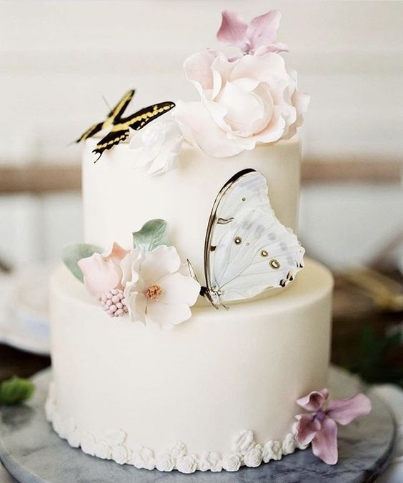 a stylish white wedding cake with sugar blooms and leaves and a couple of beautiful butterflies is amazing