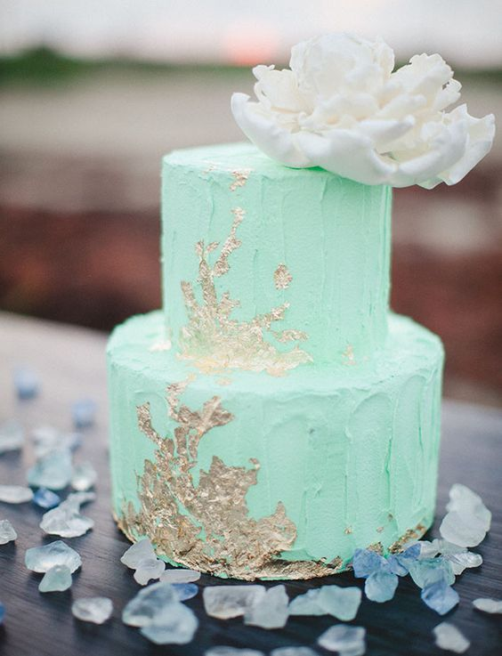 a textural mint green wedding cake with gold touches and a giant creamy sugar bloom on top