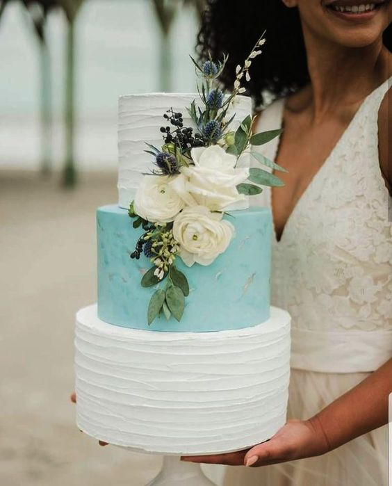 a textural wedding cake with white and tiffany blue tiers, fresh white blooms, thistles and greenery