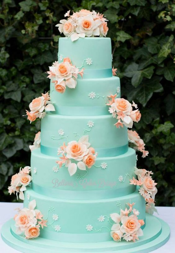 a tiffany blue wedding cake decorated with small and big sugar flowers in coral and white is a bold idea