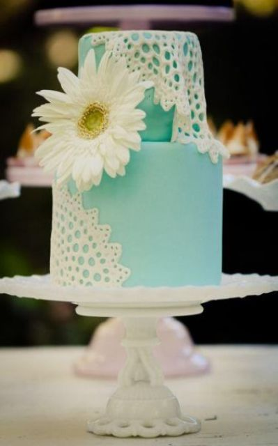 a tiffany blue wedding cake decorated with white sugar lace and a large white fresh bloom