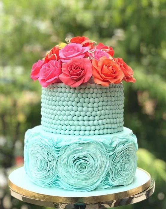 a tiffany blue wedding cake with a bead covered tier and a sugar flower one plus bold fresh blooms on top