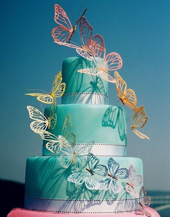 a tiffany blue wedding cake with silver ribbons and colorful rainbow butterflies is a bright and cool idea