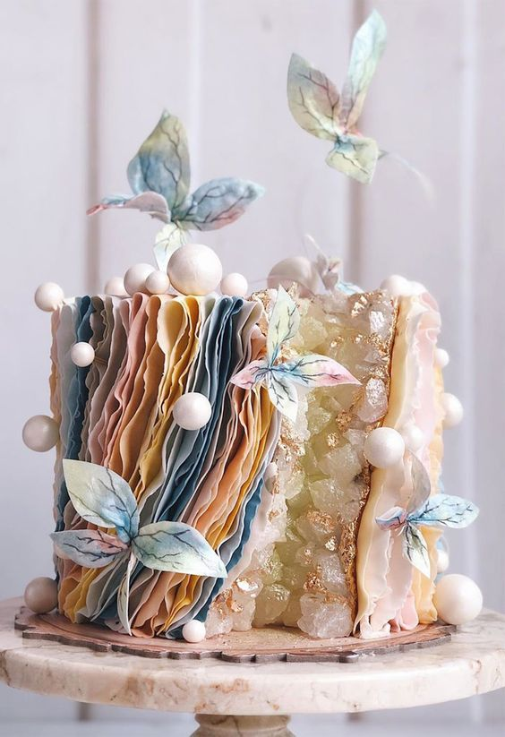 a unique wedding cake with a geode touch, layered pastel ruffles, mini snowballs, pastel sugar blooms is a lovely idea