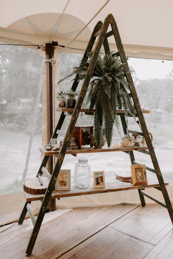 a vintage wedding decoration of a ladder, a potted plant, artworks, a wood slice and vintage decor