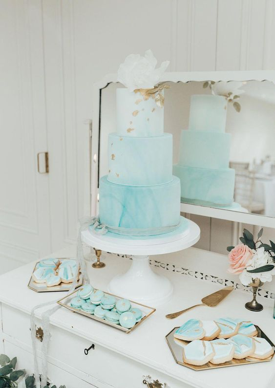 a watercolor tiffany blue wedding cake decorated with gold foil and a large white sugar bloom on top