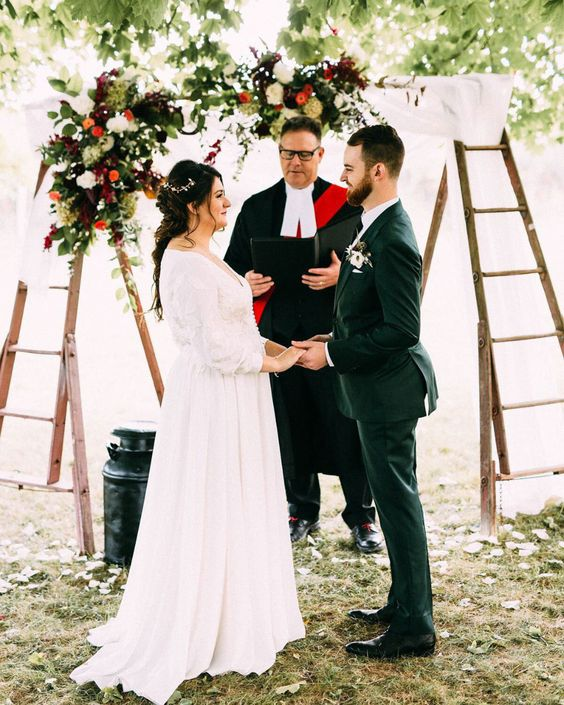 a wedding arch of ladder, airy fabric and bright florals and greenery is a cool idea for a rustic wedding