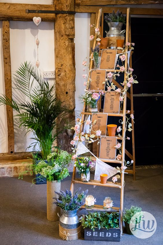 a wedding decoration of a ladder, pink blooms, greenery, white buntings and a seatign plan plus candles