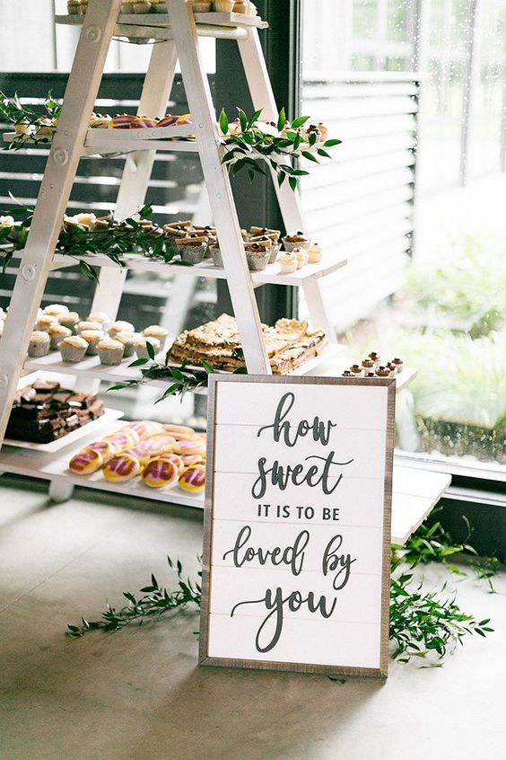 a wedding dessert station of a white ladder, greenery and desserts of various kinds is a very cool idea