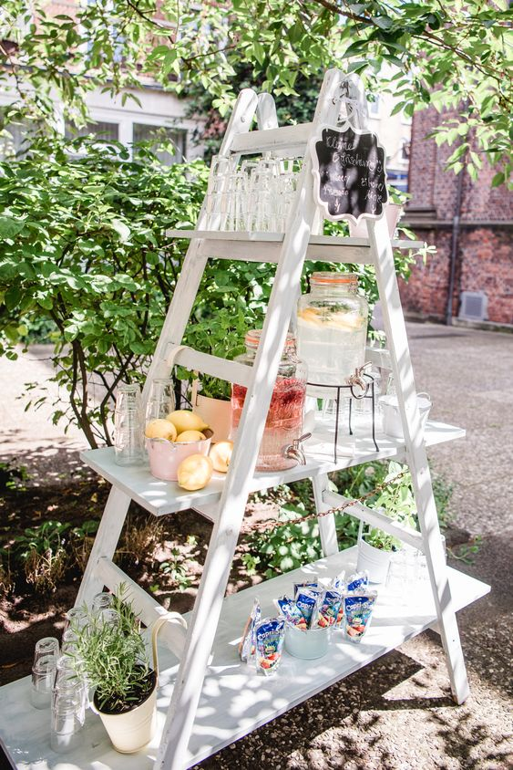 a wedding drink station of a white ladder, a chalkboard and potted greenery