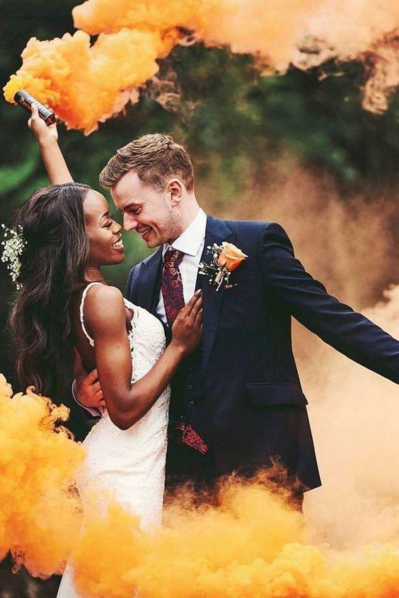 a wedding portrait highlighted with orange smoke bombs is amazing and veyr fun, filled with bright colors