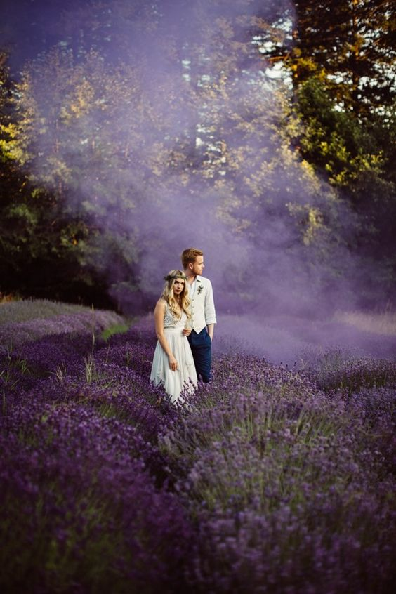 a wedding portrait in a lavender field with purple smoke around is amazing and very chic