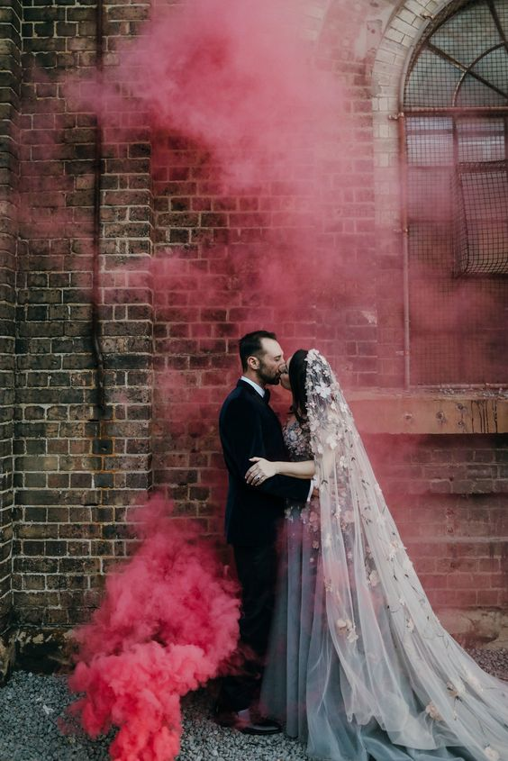 a wedding portrait with a brick wall and pink smoke backdrop that echoes with the wedding dress detailing
