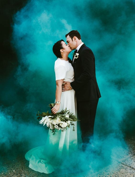 a wedding portrait with the couple in black and white and a green smoke bomb that covers them with smoke and separates from the rest of the world