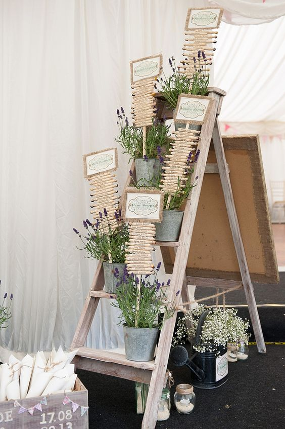 a wedding seating chart with lots of lavender in buckets and a seating plan composed of wooden beams and signs