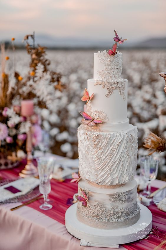 a whimsical wedding cake done in grey and white, with plenty of texture and pink and orange butterflies is a lovely and bold idea