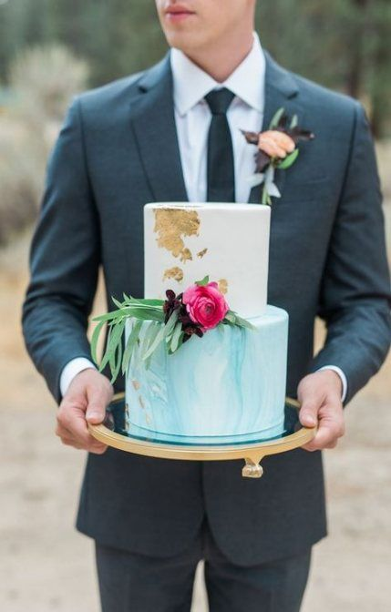 a white and watercolor tiffany blue wedding cake decorated with gold leaf, greenery and bright blooms