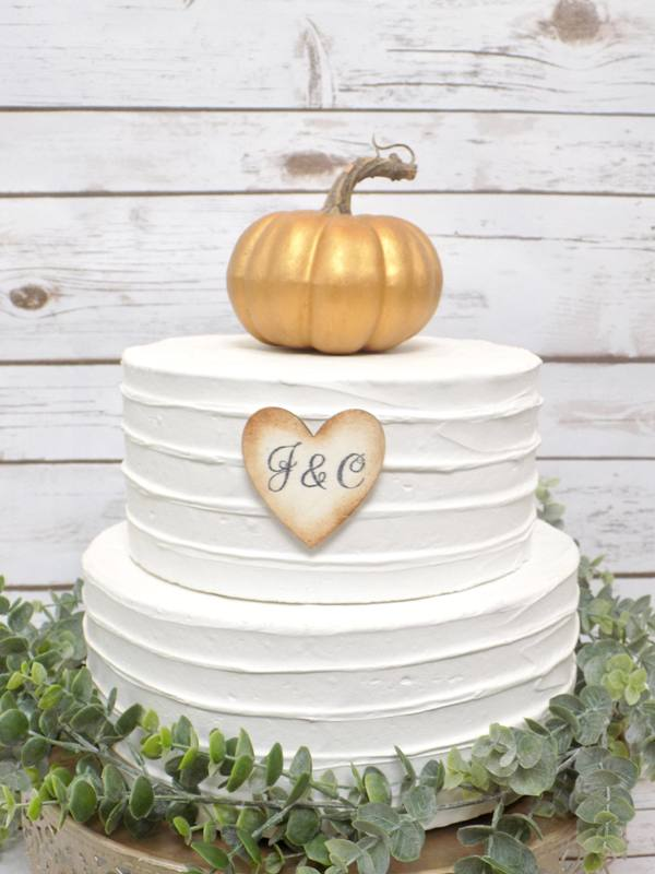 a white buttercream wedding cake with a faux gold pumpkin on top and a monogram cookie is a lovely idea for a rustic wedding