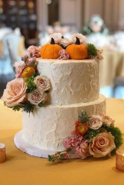a white buttercream wedding cake with a texture, sugar pumpkins, pink and blush blooms and greenery is all cool