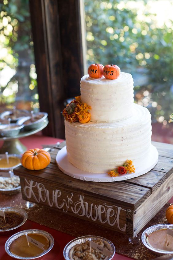 a white buttercream wedding cake with bright blooms and small edible pumpkins on top that act as cake toppers
