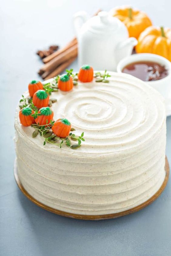 a white buttercream wedding cake with greenery and sugar pumpkins on top is a simple and cute idea for a fall wedding