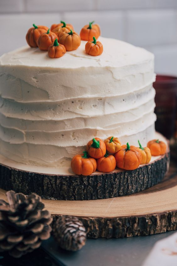 a white buttercream wedding cake with mini sugar pumpkins on top and around it is a cheerful idea for a fall rustic wedding