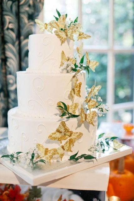 a white patterned cake with greenery and gold butterflies and baby's breath is very beautiful and natural