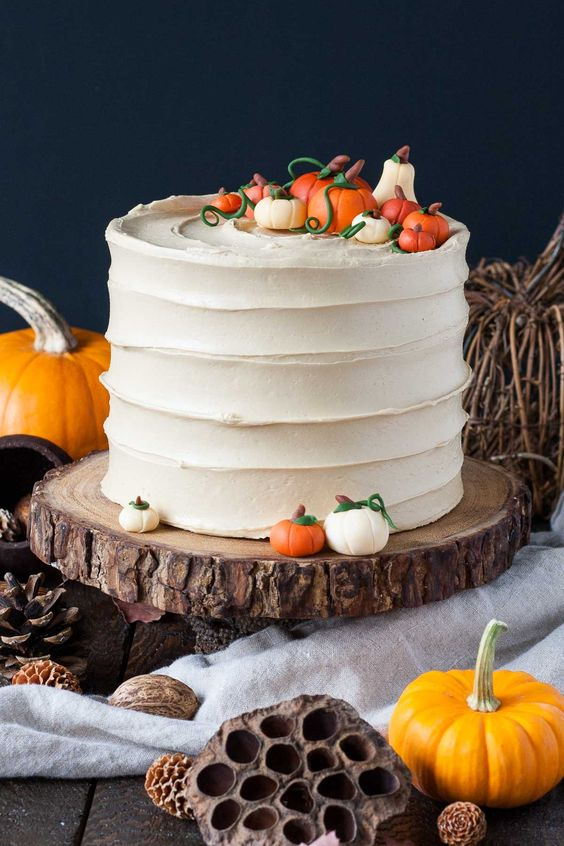 a white textural buttercream wedding cake topped with sugar pumpkins and twigs is a fun idea for a rustic fall wedding