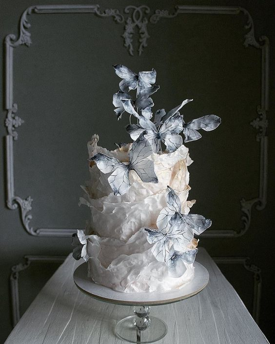 a white textural wedding cake with black and white sugar butterflies looks as if it's in motion and is very stylish and catchy