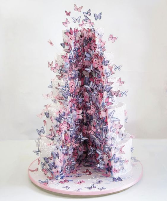 a white wedding cake cut out and with plenty of pink and purple butterflies flying out of it is a lovely and refined idea