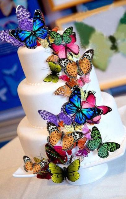 a white wedding cake decorated with colorful butterflies all over looks whimsical and magical