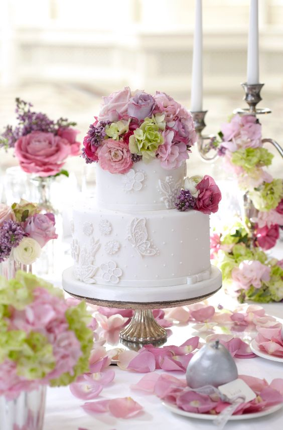 a white wedding cake decorated with flowers and butterflies plus pink and lilac blooms and greenery on top
