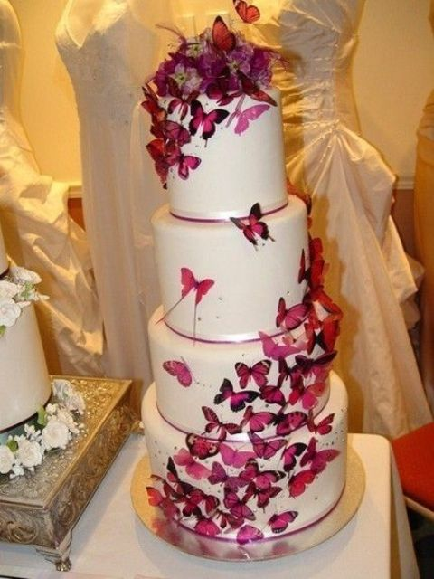 a white wedding cake decorated with lots of purple butterflies and ribbons is a lovely and bold idea that looks fairy-tale-like