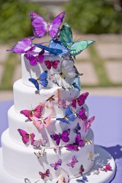 a white wedding cake decorated with purple, green, white and pink butterflies looks very chic and very eye-catchy