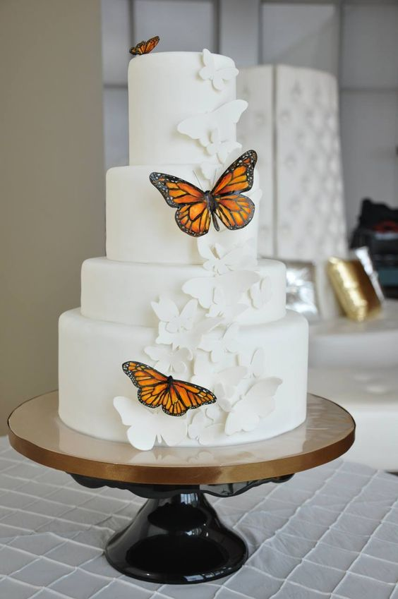 a white wedding cake decorated with white sugar butterflies and bold usual ones is a pretty and chic idea to rock