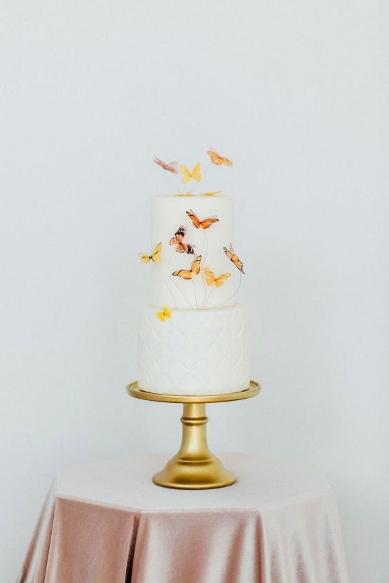a white wedding cake topped with some natural-looking butterflies on wire is a lovely and bold idea that you can realize yourself