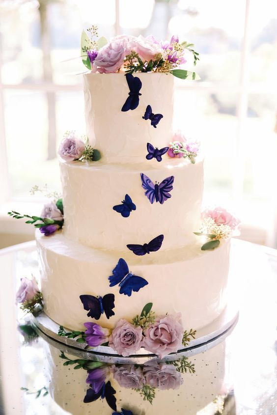 a white wedding cake with bold blue and purple butterflies and blush and lilac blooms and greenery is very fairy-tale like