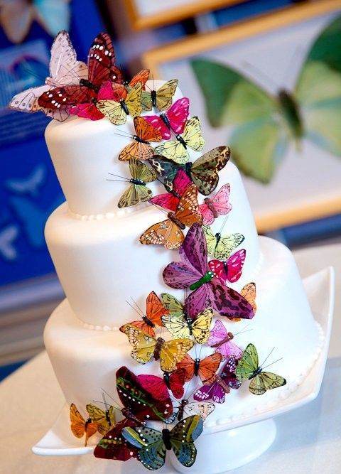 a white wedding cake with lots of colorful butterflies is a bold and cool idea of a wedding dessert to rock