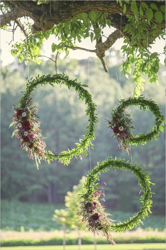 a whole arrangement of fall wedding wreaths covered with greenery, with pink, blush and deep red blooms is a lovely decoration