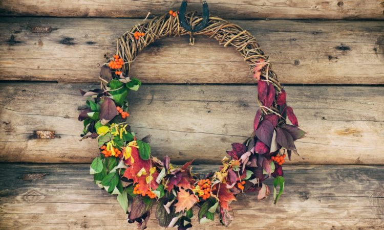 a wine wreath covered with greenery, dark foliage, berries and bright leaves is an all-natural fall wedding idea