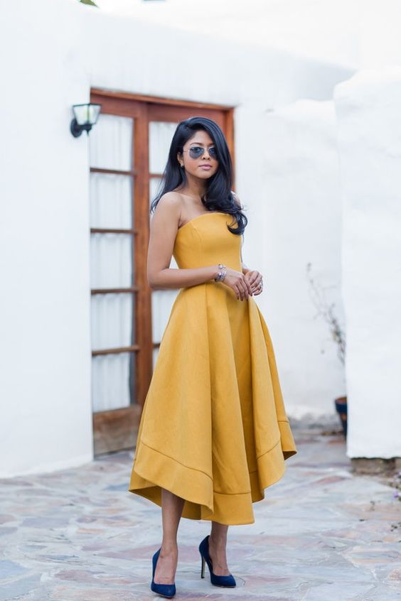 a yellow strapless midi dress with a high low skirt, pleats and navy velvet heels for a refined wedding guest look