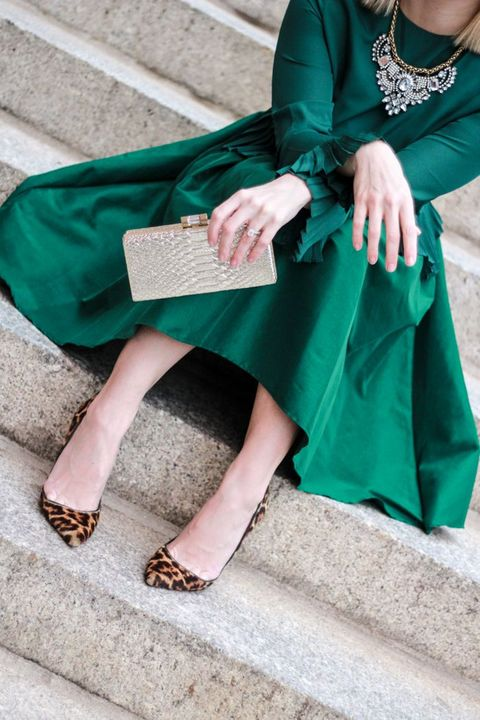 an A-line emerald skirt, a matching long sleeve top, a statement necklace, leopard shoes and a metallic clutch